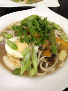 Udon noodles in a chicken drumstick stock with carrots, boiled egg, baby corn, pea snaps and scallion